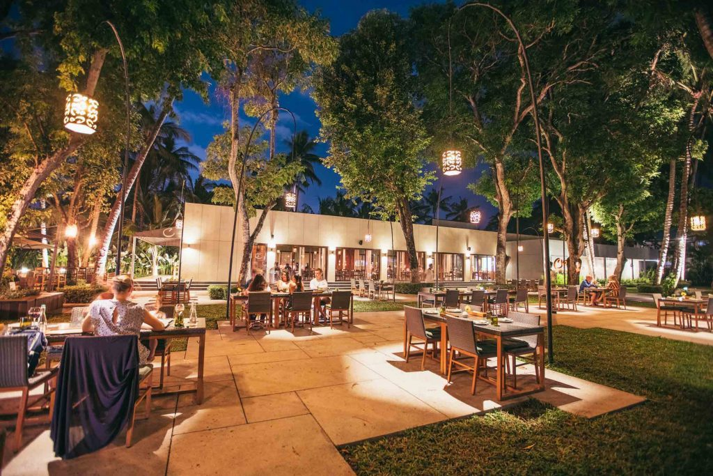 A group of people is having meal in the outdoor space of Cuca restaurant